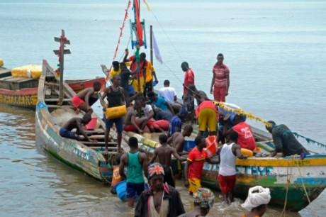 Guinée - 3 pirogues de pêches avec plusieurs pêcheurs artisanaux debout pour la plupart.