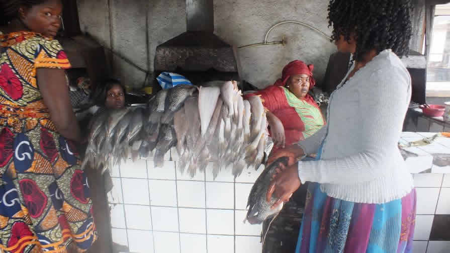 2 women standing in front of a pile of fish with other 2 women sitting behind the fish pile, serving customers.