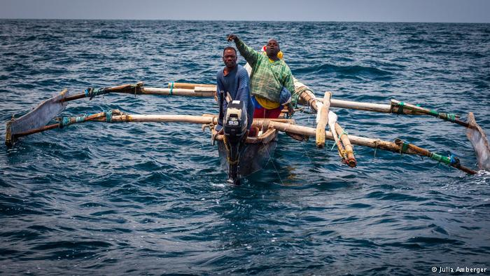 2 African men on a locally wooden made boat on the sea.