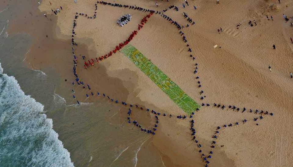 (Photo: An aerial picture shows 400 students gathering to form a giant fish on the beach of Yoff Diamalaye in Dakar to draw politicians' attention to the problems of the fisheries sector. Credit: Seyllou/AFP/Getty Images)
