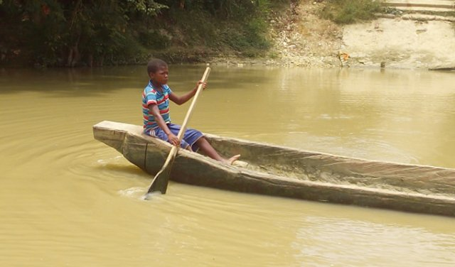 child on boat on river