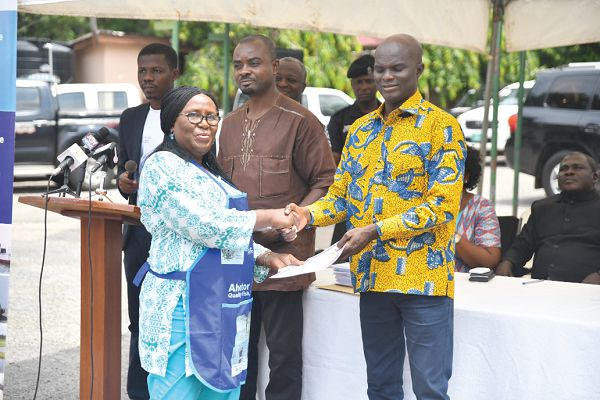 Ghana - Mr Francis Kingsley Ato Codjoe presenting a certificate to Madam Emelia Nortey, a beneficiary, in Accra yesterday. Picture: EMMANUEL QUAYE