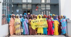 """Senegalese fish processor women hold a banner reading « Women United against Fishmeal » outside the Fisheries Minister building, after a meeting to present their demands to the authorities to stop fishmeal and fish oil production in West Africa. Greenpeace is in Dakar as part of the """"Protect the Oceans"""" tour, a year long pole to pole expedition. The aim of the expedition is to raise awareness among decision-makers and the international community of the need to protect the oceans and to safeguard biodiversity and ensure the sustainable use of the resources on which many of the world's poorest and most vulnerable people depend."""