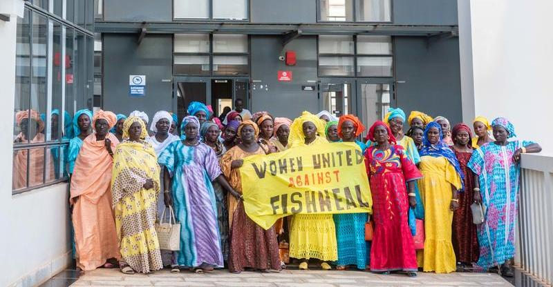 "Senegalese fish processor women hold a banner reading « Women United against Fishmeal » outside the Fisheries Minister building, after a meeting to present their demands to the authorities to stop fishmeal and fish oil production in West Africa. Greenpeace is in Dakar as part of the ""Protect the Oceans"" tour, a year long pole to pole expedition. The aim of the expedition is to raise awareness among decision-makers and the international community of the need to protect the oceans and to safeguard biodiversity and ensure the sustainable use of the resources on which many of the world's poorest and most vulnerable people depend."